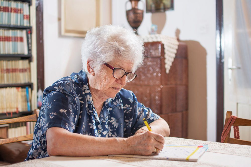 Elderly woman with eyeglasses sitting near the table and doing crossword.