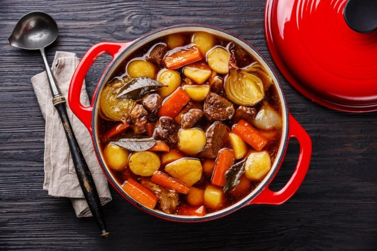 Beef meat stewed with potatoes, carrots and spices in cast iron pot on burned black wooden background
