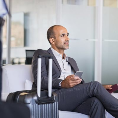 Mature businessman expecting airplane at the airport. Thoughtful business man waiting for flight in airport. Formal business man sitting in airport waiting room with luggage and phone in hand.