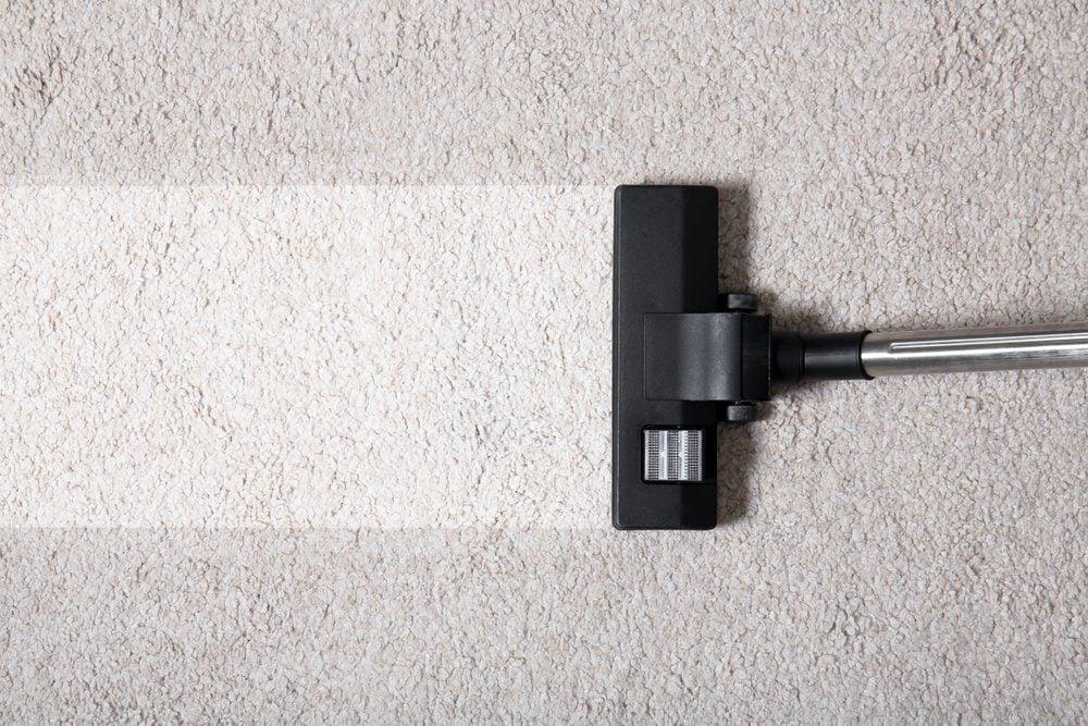Vacuum cleaner on carpet indoors, closeup. Cleaning service