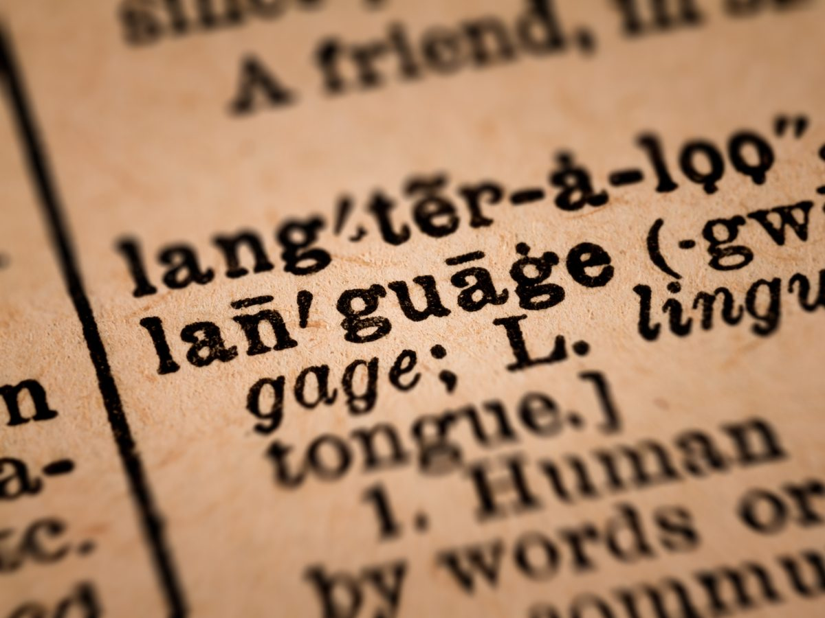 "Close-up of the word ""language"" in vintage dictionary"