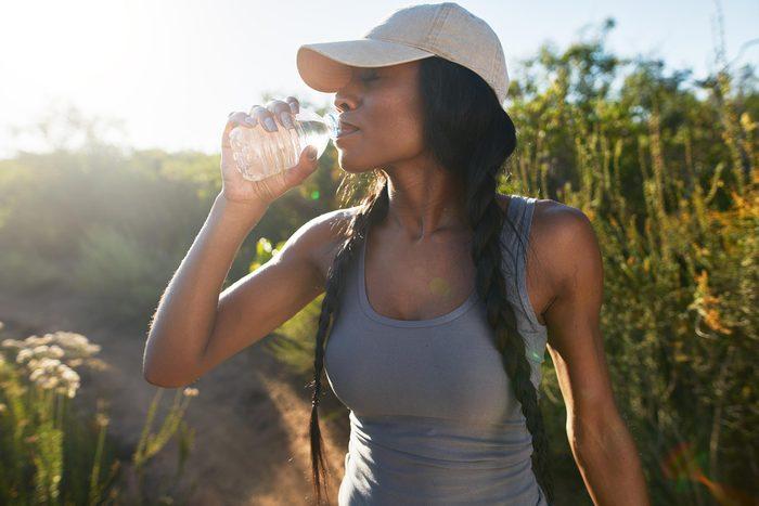 woman drink water sun flare