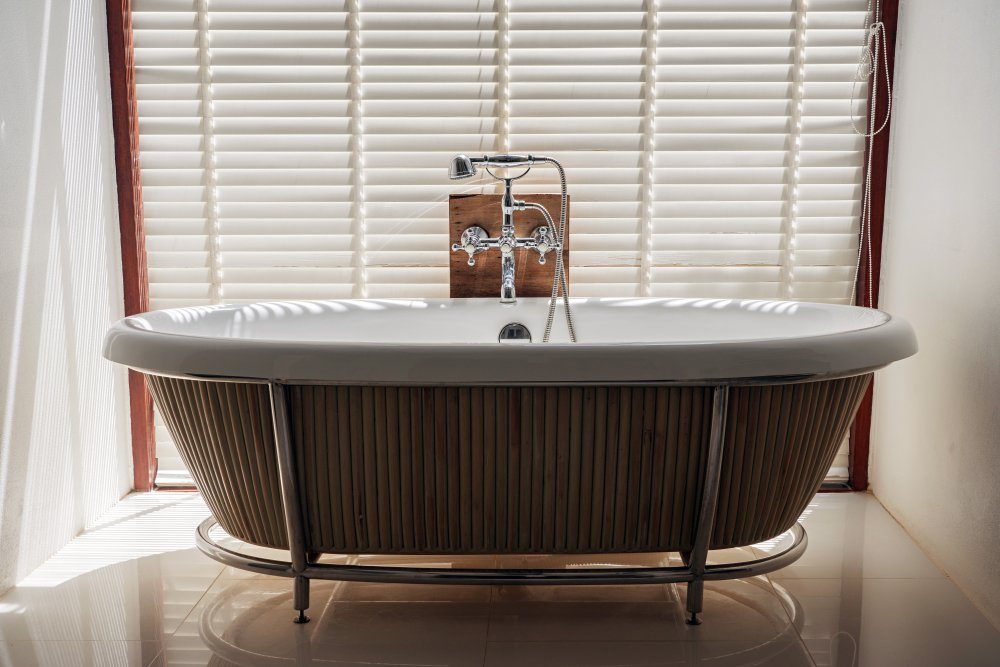 White bathtub with steel faucet and shower head on white wooden chick blind background.