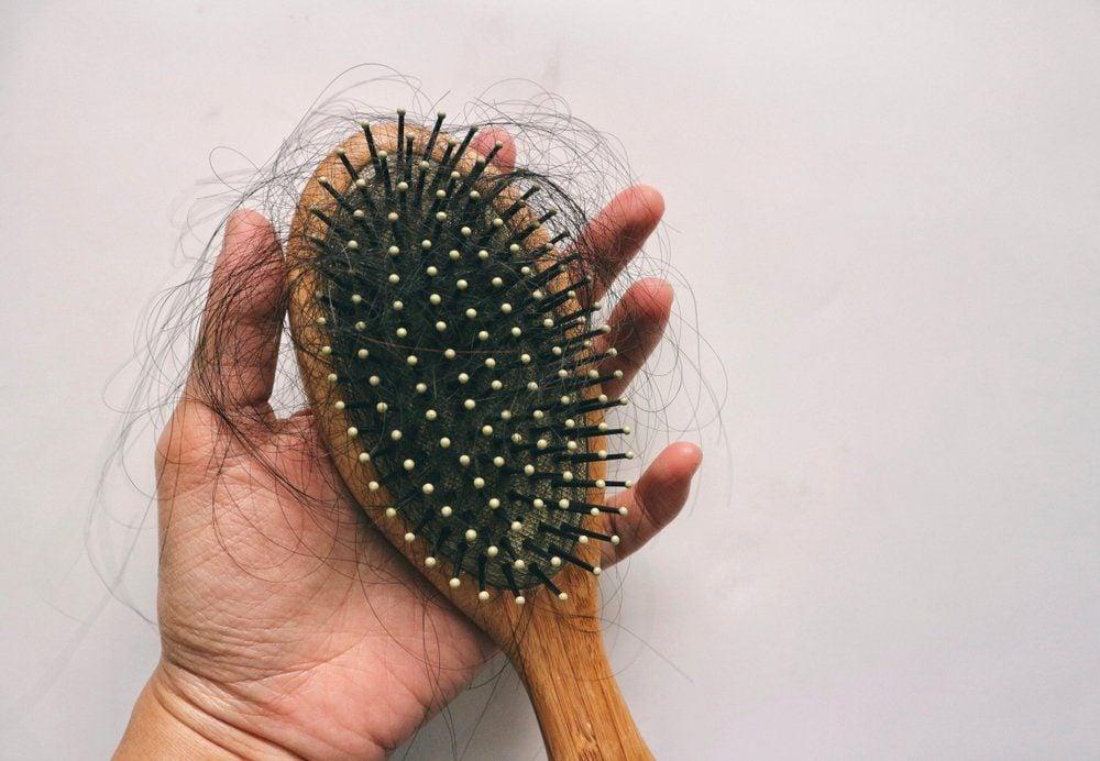 Hair loss inside wood comb brush, on hand