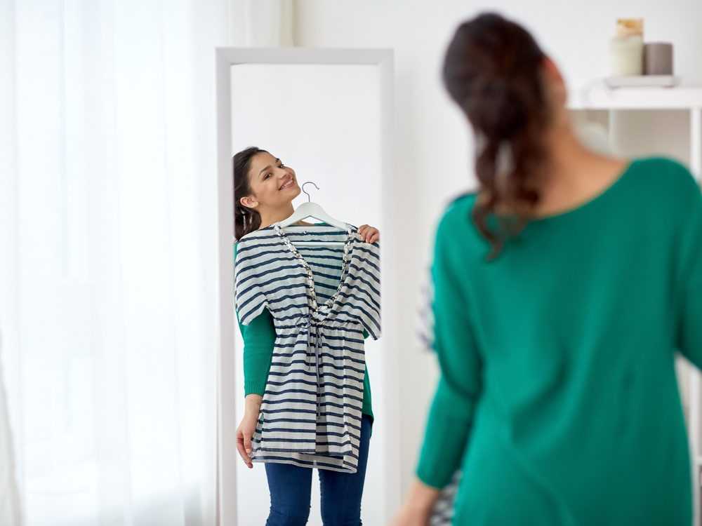 Woman trying on clothes in the mirror