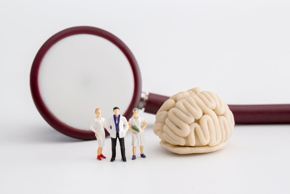 "Miniature doctor and nurse ""team specialists"" observing and discussing about human brain, Science and Medical Concept"
