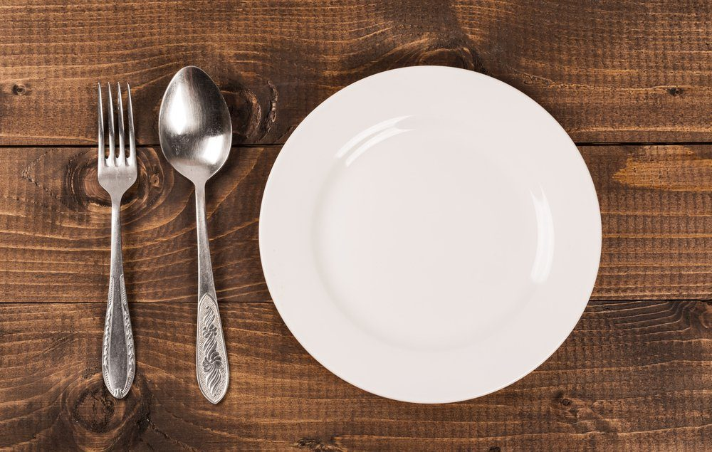 Empty white plate with silverware on wooden table. View from above