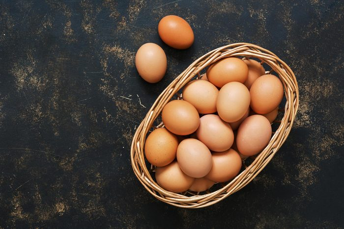 Foods everyone over 50 should be eating - Brown eggs in a basket on an old dark surface. Top view, space for text
