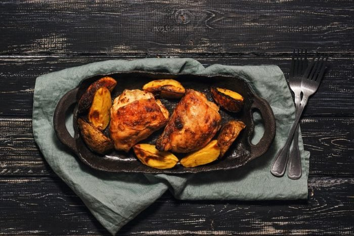 Chicken thigh baked with potatoes on a black dish. Rural background, top view
