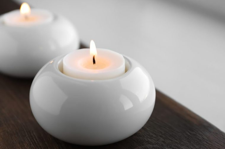 Beautiful burning wax candle in holder on table