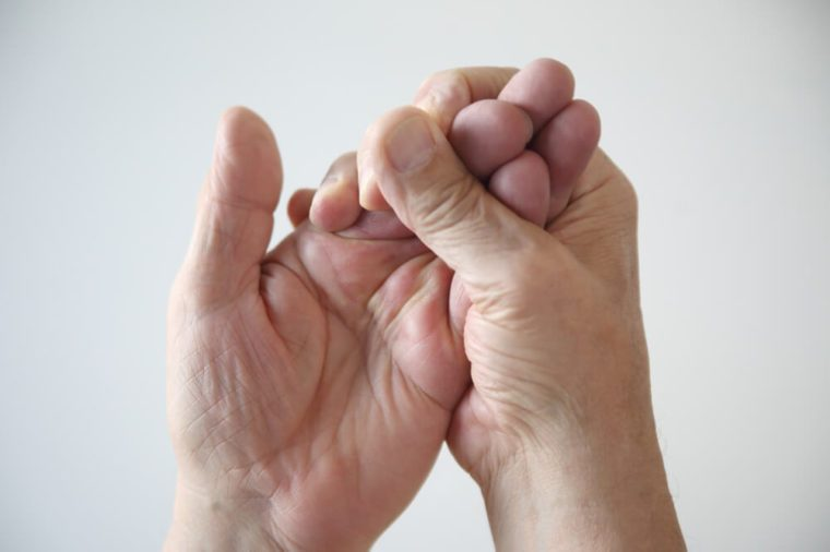 a man tries to restore feeling in his numb hand