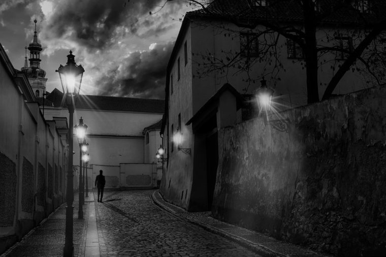 Alley of Prague (located in the Nový Svět area, part of the Hradčany district) with a silhouette of a man walking and several street lights on.