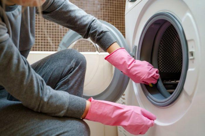 Image of female hands in pink rubber glove washing washing machine