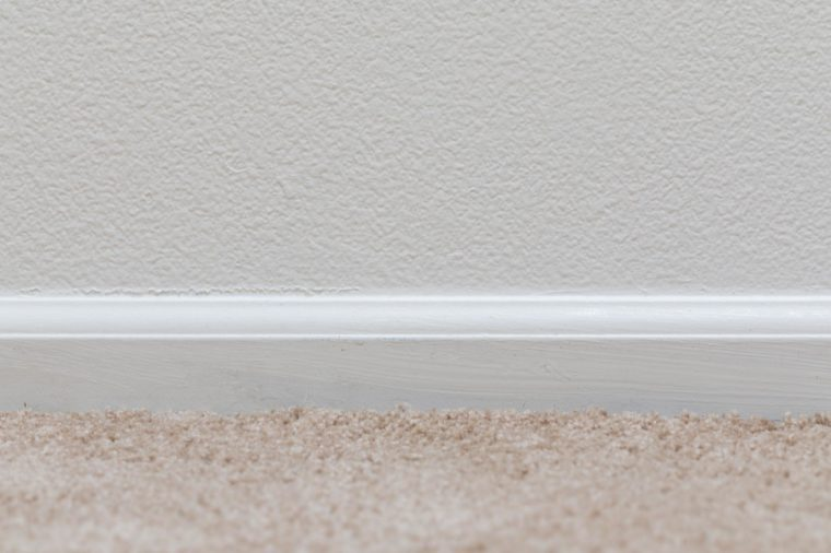 Basic floor trim up against a tan carpeted floor