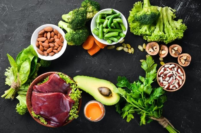 Food containing natural iron. Fe: Liver, avocado, broccoli, spinach, parsley, beans, nuts, on a black stone background. Top view.