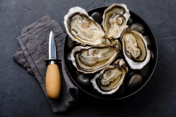 Fresh Oysters with lemon and knife on stones on dark background