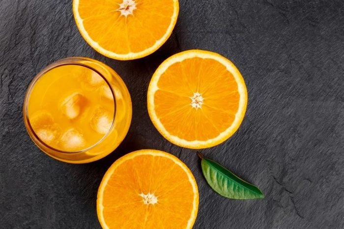 A closeup photo of a glass of fresh orange juice with ice cubes, orange halves and a green leaf, shot from the top on a black background with a place for text