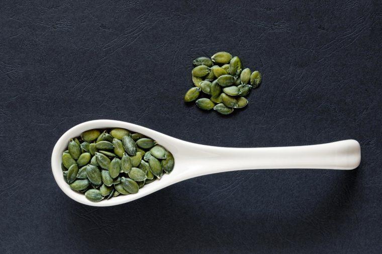 Raw pumpkin seeds in a porcelain spoon an a dark textured background