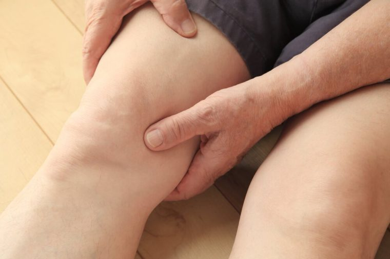 Older man indicates area of pain on his thigh.