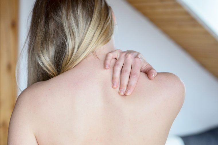 Rear upper body view of young woman rubbing painful shoulder with hand
