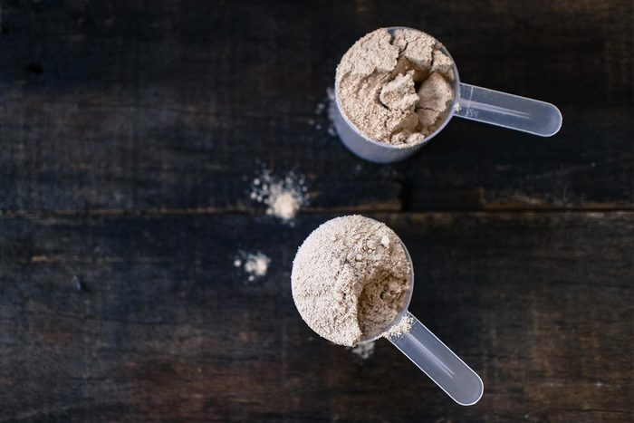 Foods everyone over 50 should be eating - Whey powder in measuring scoops on wooden background.