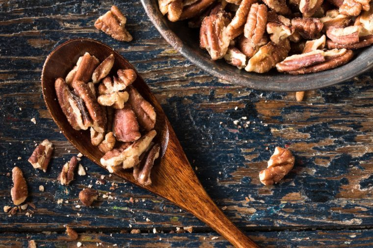 Chopped pecans on a wood spoon