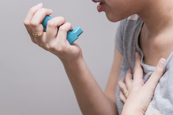 Asian woman using a pressurized cartridge inhaler extended pharynx, Bronchodilator