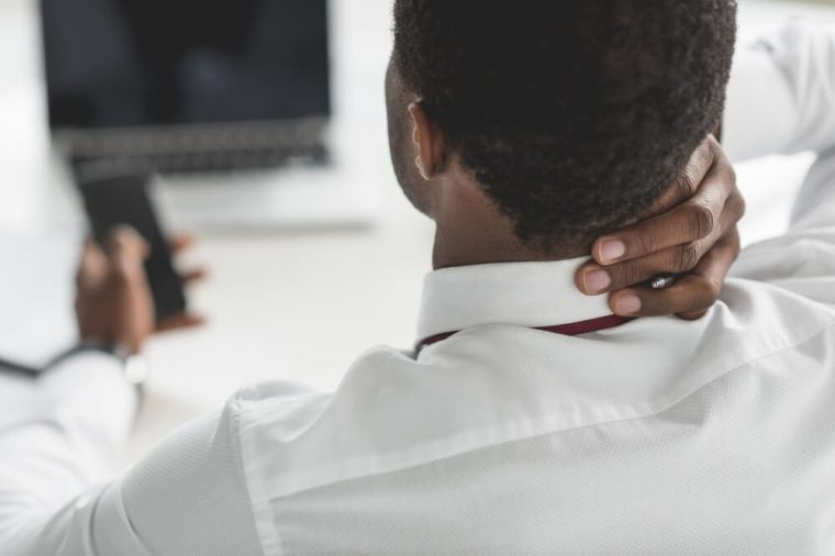 selective focus of african american businessman having neck ache at workplace