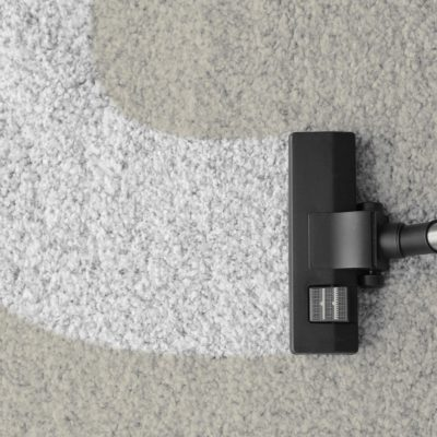 Vacuum cleaner removing dirt from carpet