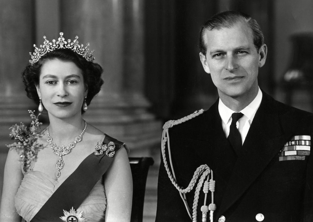 Historical Collection 172 Queen Elizabeth Ii and Prince Philip Duke of Edinburgh Pictured Together in the Grand Entrance in Buckingham Palace in 1954 the Queen is Wearing A Yellow Tulle Evening Gown Decorated with Sprays of Mimosa and Gold Pailette Embroidery and is Wearing the Blue Ribbon and Star of the Garter Her Necklace Was A Wedding Present From the Nizam of Hyderabad; the Tiara Also A Wedding Present From Queen Mary the Bow Brooch and Drop Earrings Are Set with Diamonds the Duke is Wearing the Uniform of the Admiral of the Fleet 1954