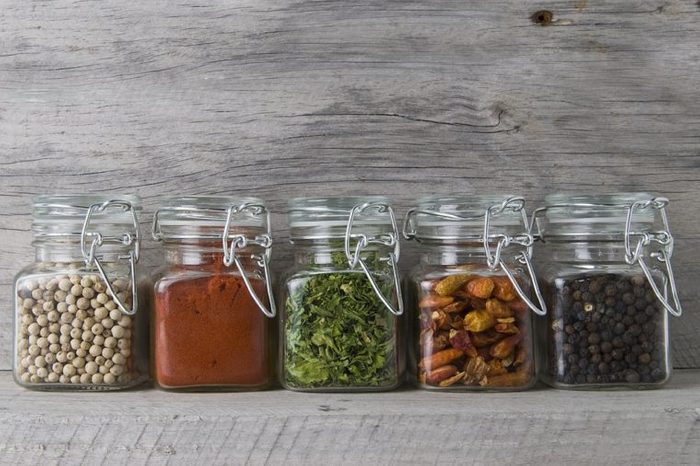 Glass jars with some spices on an old wooden stand.