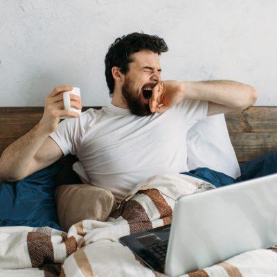 man bed tired yawning