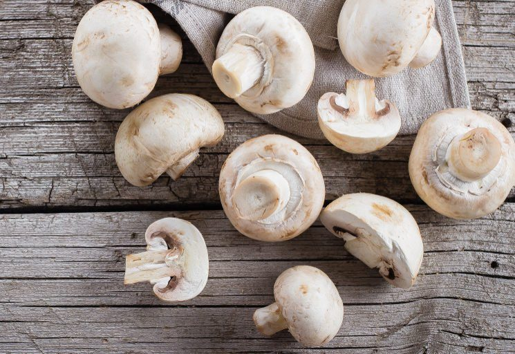 Fresh mushrooms champignons on a wooden background. Autumn Harvest Food Vegetarian Vegetable. Top View, Copy Space
