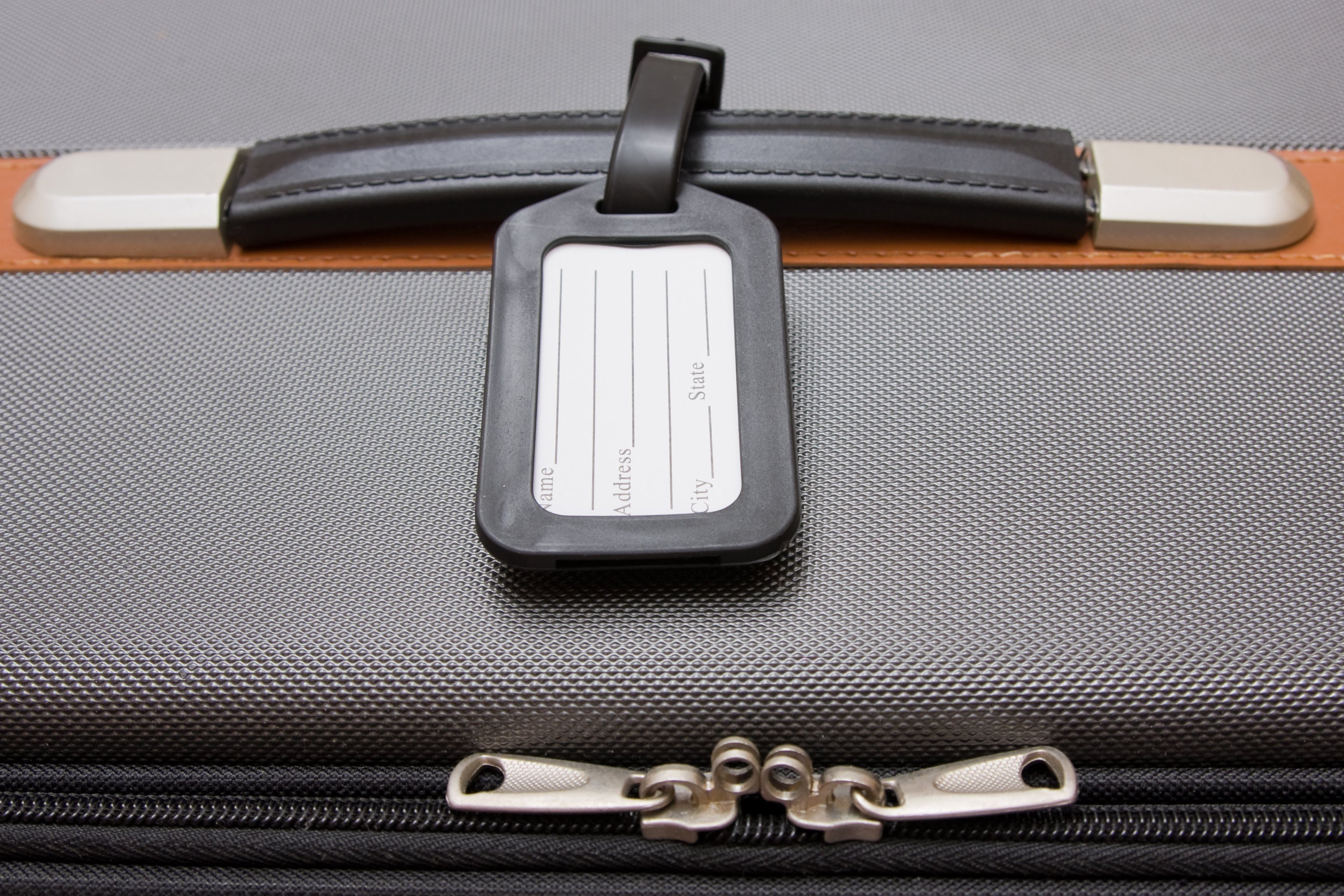 A black luggage tag on a handle on a bag