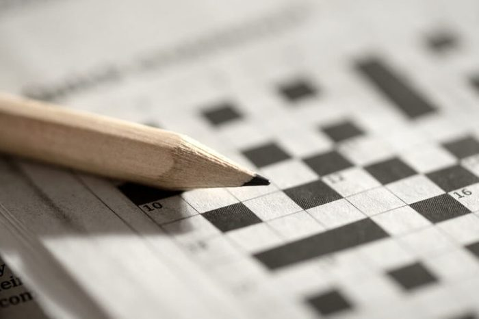 Close up view of a blank crossword puzzle grid with black and white squares and a pencil