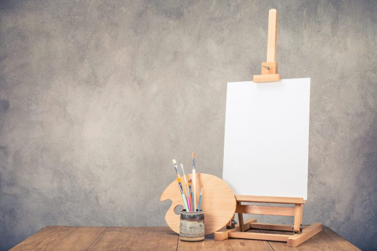 Portable desk easel for painting with canvas blank, brushes and artist's palette on wooden table front concrete wall background. Retro style filtered photo