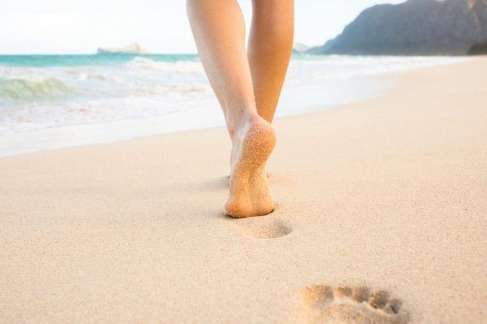 Beach travel - woman walking on sand beach leaving footprints in the sand. Closeup detail of female feet and golden sand on Maui, Hawaii, USA.