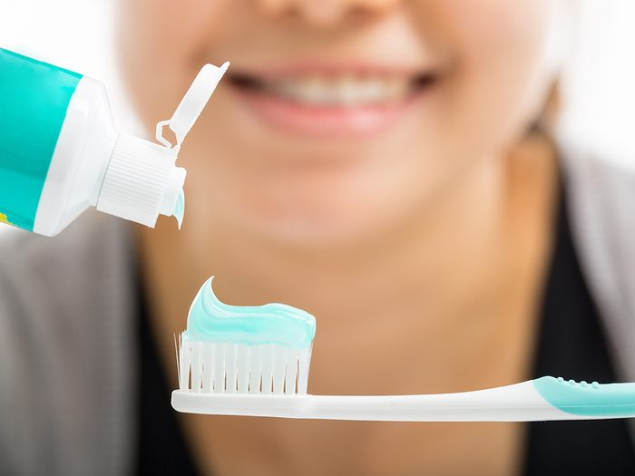 How long you should brush your teeth for - woman squeezing toothpaste onto toothbrush