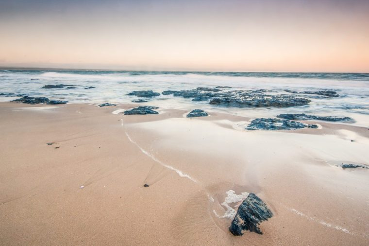Rough sea and golden sand at the rugged coast in jeffrey's bay,South Africa. This is the most famous location for surfing in africa ,