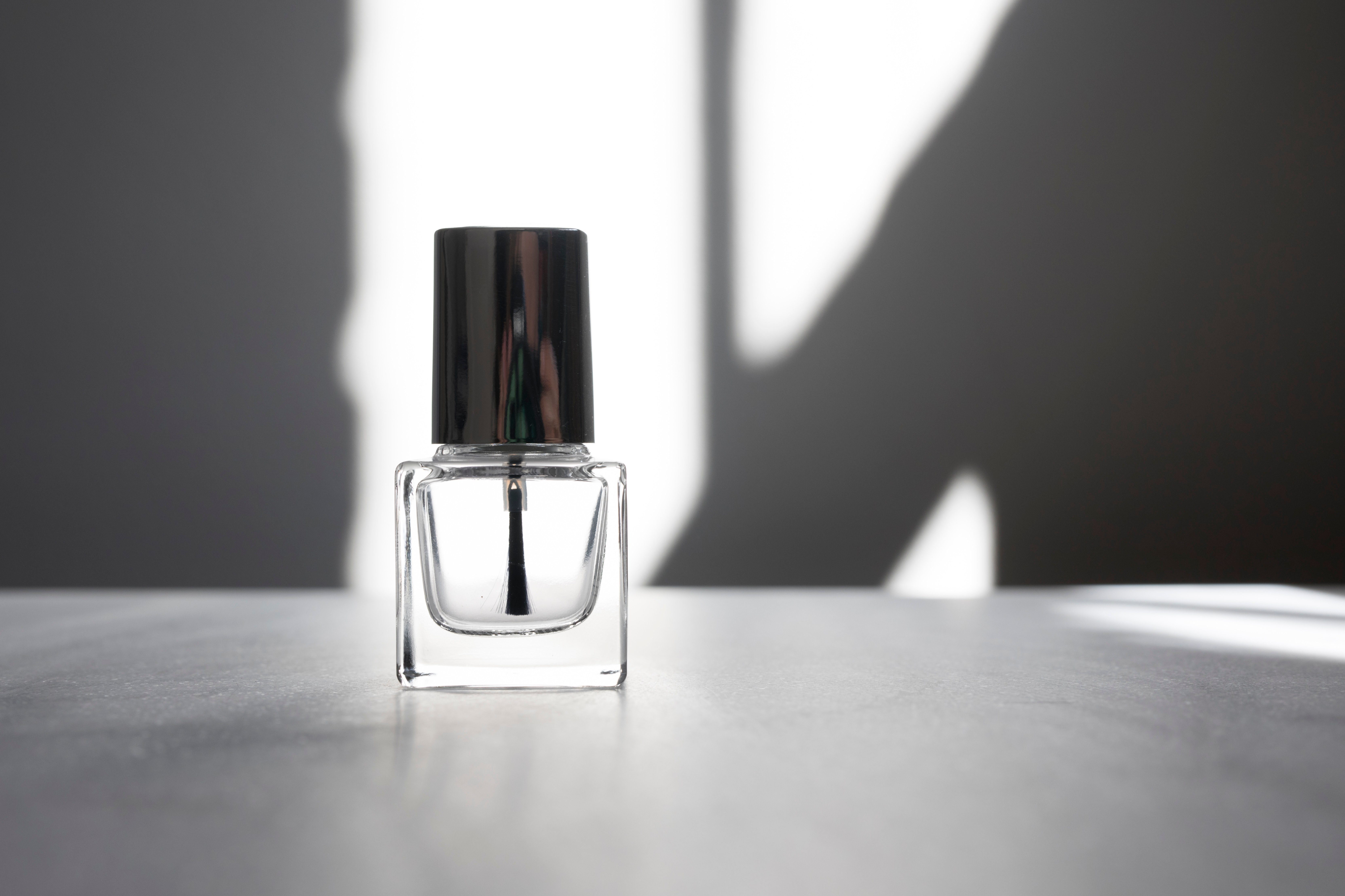 View of a simple clear glass nailpolish bottle with silver top against a white background which shdows cast by a near by window