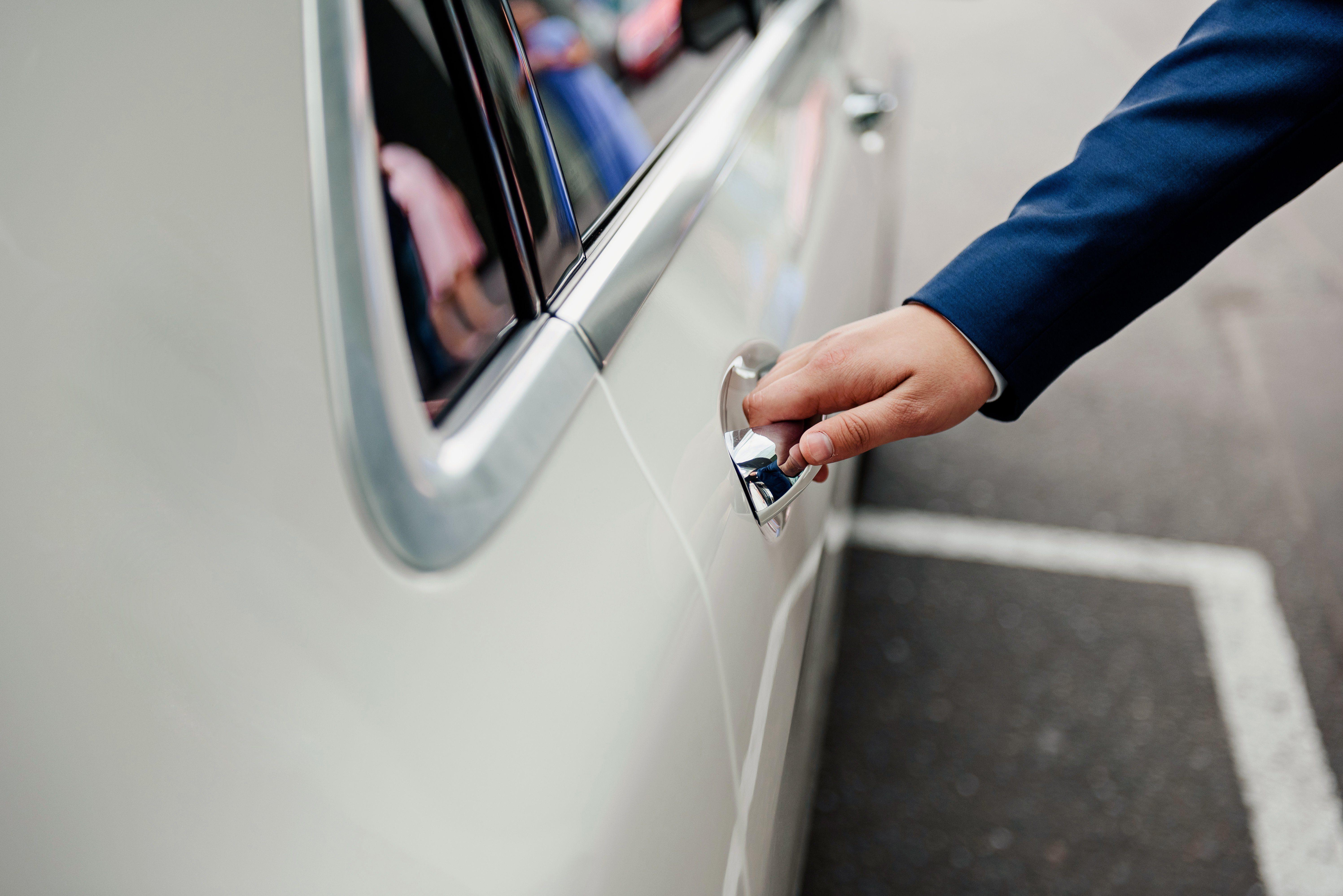 The groom opens the car door