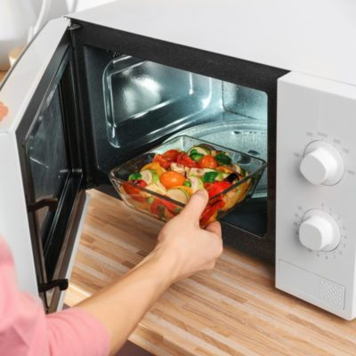 Woman putting bowl with vegetables in microwave oven