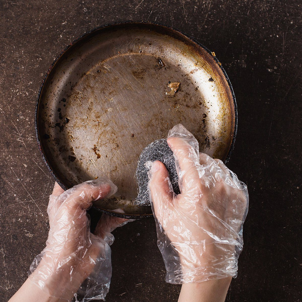 Wash the frying pan on a dark marble background.