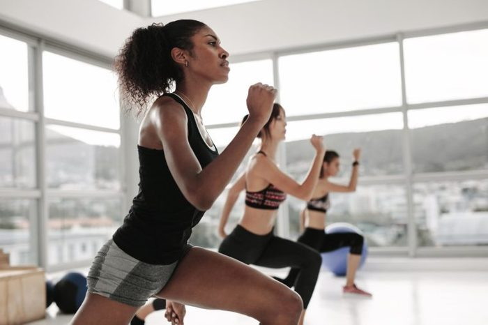 Young woman in sportswear doing exercise during intensive circuit training in gym class. Females working out together in the health studio.