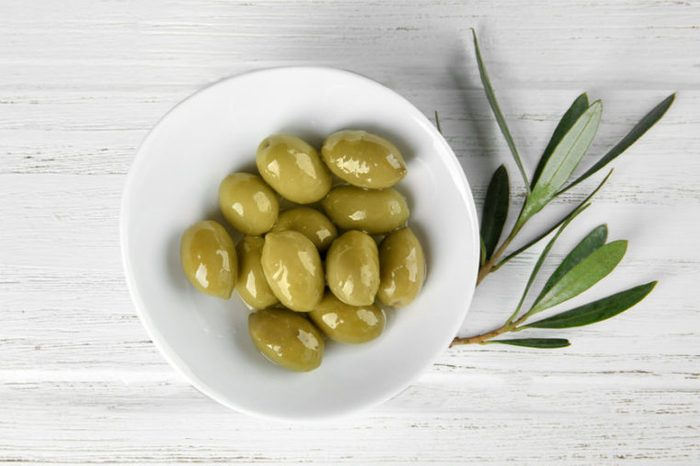 Plate with canned olives on wooden table