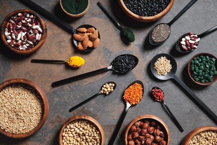 top view of wooden bowls and spoons with superfoods, legumes and grains on table