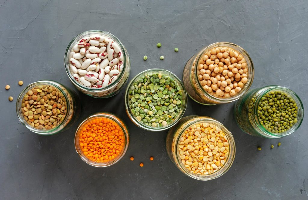 Died lentils and pulses in open glass kitchen jars for storage view top down, healthy ingredients for vegetarian cuisine