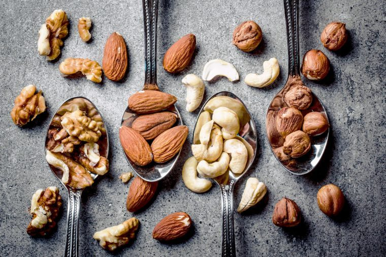 Walnuts, hazelnuts, almonds and cashew on metal silver spoons.