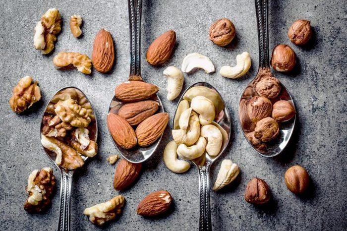 Walnuts, hazelnuts, almonds and cashew on metal silver spoons.