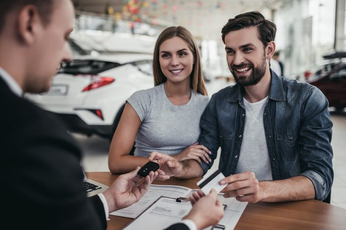 Happy beautiful couple is buying a new car at dealership. Credit card in hand.